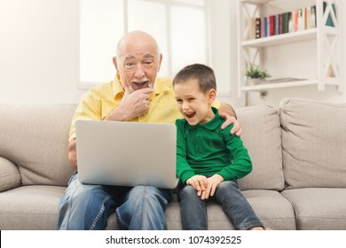 Little boy teaching his grandfather how to use internet safety. Surprised senior man using laptop, laughing with his grandson, sitting on sofa at home, copy space