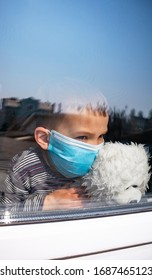 Little boy with teddybear wearing surgical mask looking out through window. Coronavirus quarantine during the COVID-19 epidemic.