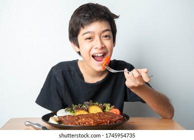 Kleiner Teenager, der Tomate mit Salat zu seinem Essen isst