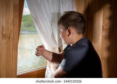 A little boy, a teenager looking out the window. The window in the room, wooden decoration.