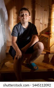 A little boy, a teenager sitting on a wooden staircase and looking in the room of the house.