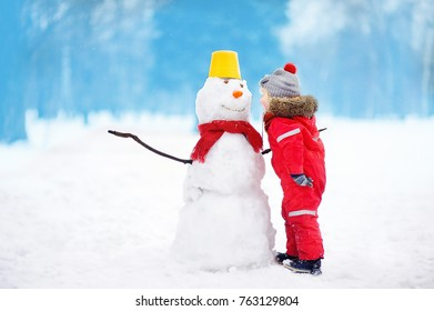 Little boy tell snowman about his secrets or gifts for Christmas. Active outdoors leisure with children in winter. Kid during stroll in a snowy winter park