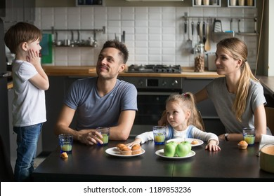 Little boy telling story, poems standing on chair at breakfast, mother, father, daughter listening to son, brother, happy family dine, spending time together