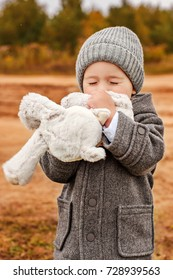 little boy tenderly kisses his toy bunny with his eyes closed