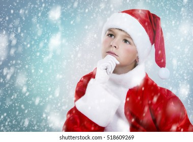 little boy thinking wearing Christmas outfit on snowy background