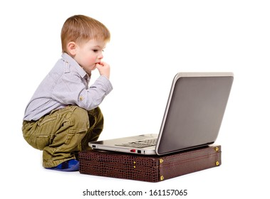 Little boy thoughtfully sits at a notebook
