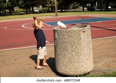 A little boy throwing away his milk cartoon in a public trash container at the park. The child is cleaning up the playground from trash and debris.  Don't litter concept.