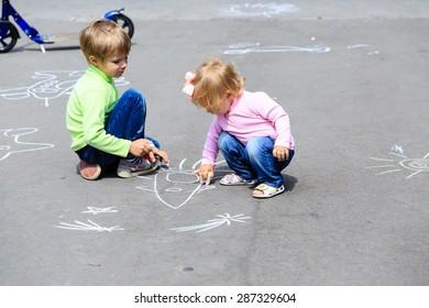 little boy and toddler girl drawing rocket on asphalt, kids outdoor activities