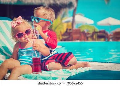 little boy and toddler girl drinking juices on beach