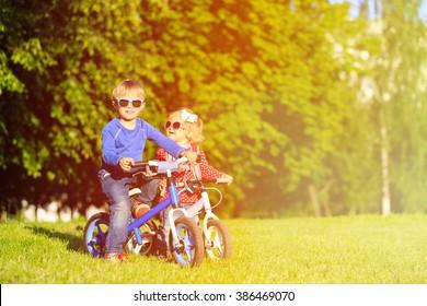 little boy and toddler girl on bikes in summer park