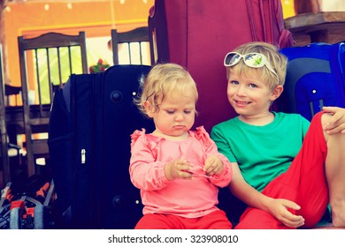 little boy and toddler girl sitting on suitcases ready to travel, kids travel concept
