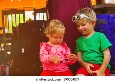 little boy and toddler girl sitting on suitcases ready to travel