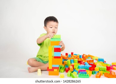 Little boy toddler playing plastic block colorful with happy