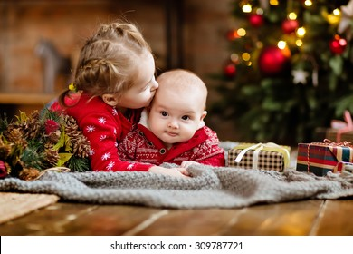 Little boy toddler in a red sweater kisses his older sister, lying together on a cozy blanket on the Christmas tree and garlands in the house next to the gifts