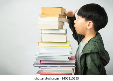 A little boy with tons of books. Library, Reading Skill, Learning, Early Education, Overload, Back to school, Child development, Bookworm, Smart kids, Genius, Intelligence, High IQ, Emotion Quotient.