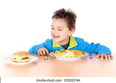 little boy torn between hamburguer and vegetables isolated in white background