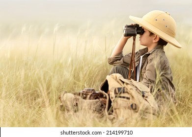 Little boy tourist looking into the distance with binoculars through the thick grass