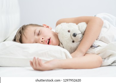 Little boy with toy bear is sleeping with his mouth open, snoring.