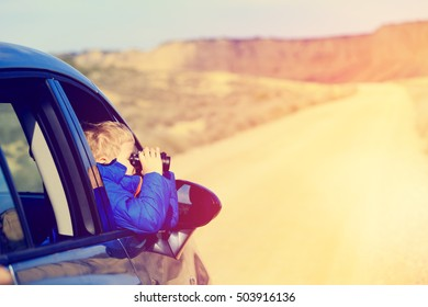 little boy travel by car on road to mountains