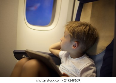Little boy traveling by plane. He looking out illuminator holding tablet PC on his lap