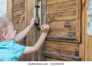 The little boy tries to open the door. The child is in front of the locked door.