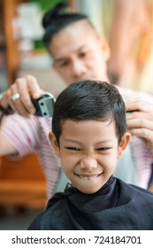 A little boy is trimmed by hairdresser and bright emotions on his face