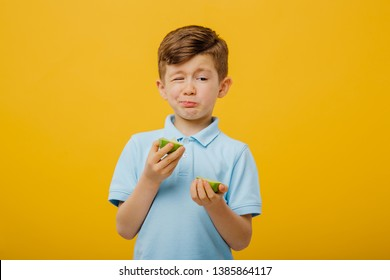little boy try to taste a fresh lime, sour taste, make grimace, facial emotions negative, in blue T-shirt, isolated yellow background, copy space