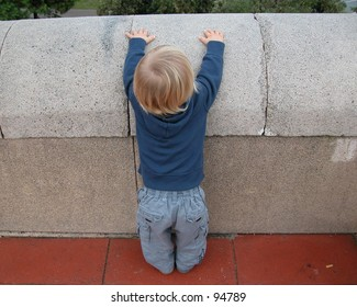 Little boy trying to climb a low wall