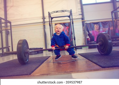 little boy trying to lift heavy weight in a gym
