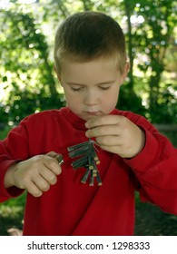 A little boy trying to light a bunch of firecrackers.