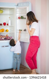 Little boy trying to pick something from fridge while his mother opening the fridge door.