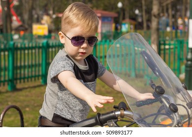 Little boy in t-shirt on motorcycle in the park