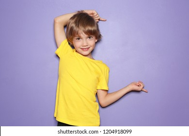 Little boy in t-shirt pointing at something on color background