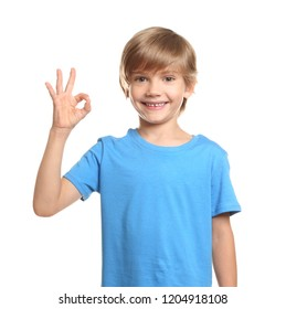 Little boy in t-shirt showing OK gesture on white background