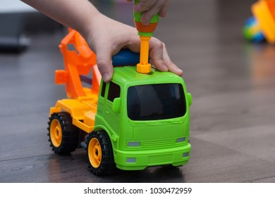 Little boy twists the bolt with a screwdriver. Kid plays with plastick toy car.