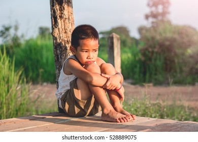 Little boy unhappy sitting alone on abandoned temporary housing.