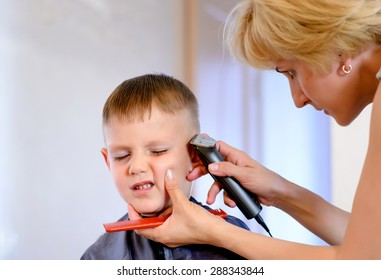 Little boy unimpressed with his haircut pulling a comical face as the hairdresser does the final trim