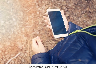Little boy uses the phone outdoors