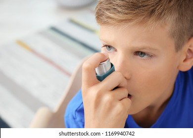 Little boy using asthma inhaler on blurred background