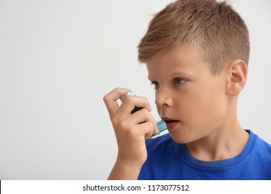Little boy using asthma inhaler on light background