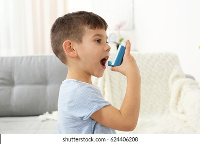 Little boy using asthma inhaler at home