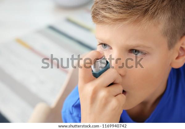 Little boy using asthma inhaler on blurred background