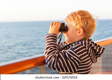 little boy using binoculars while on a cruise ship in open sea