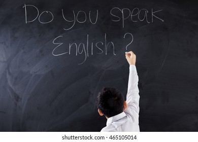 Little boy using a chalk to write text Do You Speak English on the chalkboard, shot in the class