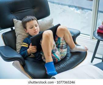 Little boy using digital tablet while lying on reclining armchair