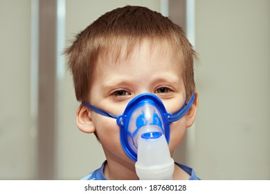 Little boy using an inhaler indoors
