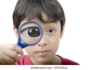 Little boy using magnifier close up on white background