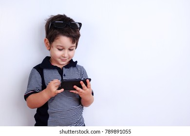 Little boy using mobile phone. Child playing on smartphone. Technology, mobile apps, children and parental advisory, lifestyle concept