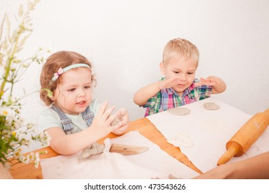 Little boy using a rolling pin that to roll modelling clay