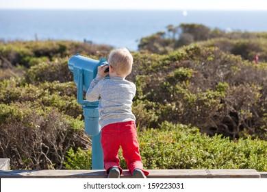 little boy using seaside binoculars outside, rear view
